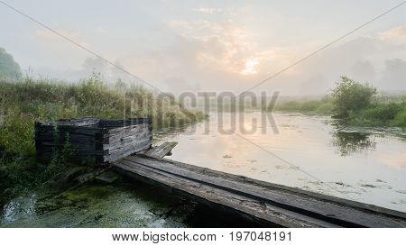 Old wooden well and bridge across small river at summer cloudy sunrise. Stray dog in fog and water reflections