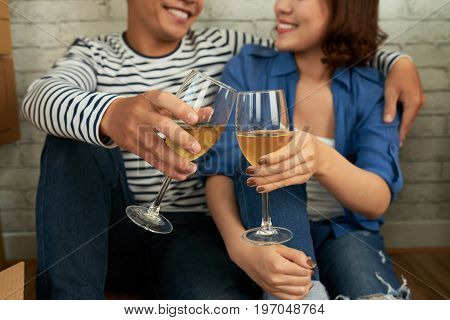Close-up shot of joyful Asian couple clinking wine glasses together while sitting on floor of new apartment