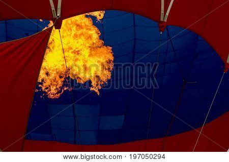 Close-up burning burner, bright flame against Hot air balloon. Preparing to launch a flying air balloon. Festival of balloons. With place for your text, for background use