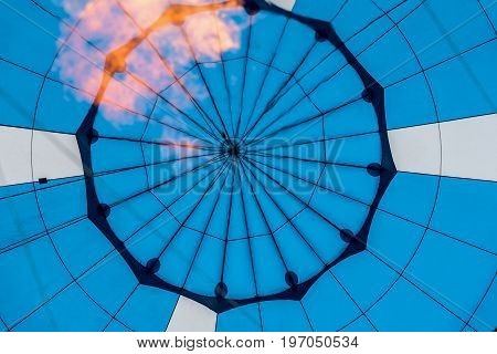 Close-up of abstract beautiful texture of geometric surface of hot air balloon, right blue colors and flame from burner. Background for bright moments of life