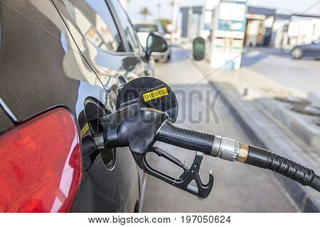 Filling up fuel tank with diesel at the self service station. Diesel vehicle