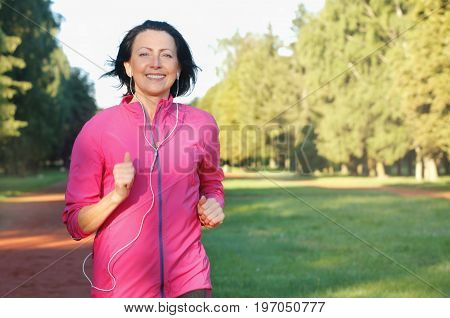 Portrait Of Elderly Woman Running With Headphones In The Park