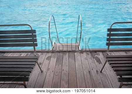 Pontoon with wooden benches and stair at sea resort in summer day