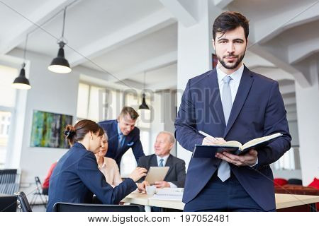 Man as consultant and controller in business meeting with team in the back