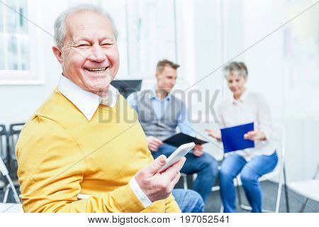 Successful senior man as consultant holds smartphone and smiles with joy