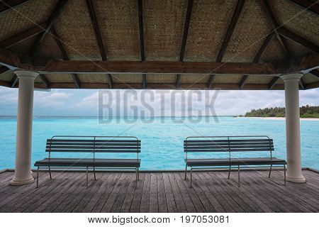 Shelter shed and wooden benches at sea resort on summer day