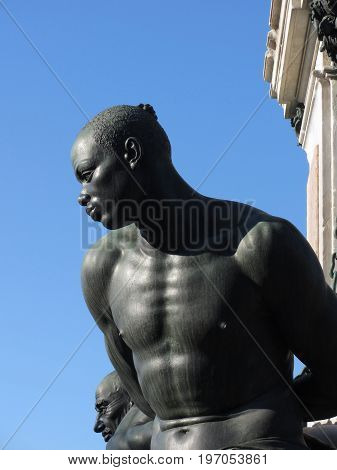 The monument Quattro Mori ( of the Four Moors ) in Livorno city . View of one of the four moors against the blue sky . Tuscany Italy
