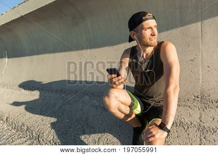 Handsome fit sportsman listening to music with earphones while resting after work out outdoors