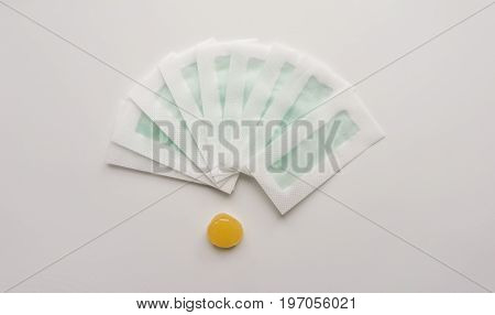 Tool, instrument for hair depilation: sugaring and wax strips on a white background. Top. Close-up. Stock photo.