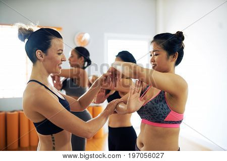 Multi-ethnic group of talented women rehearsing contemporary dance while their middle-aged coach helping them with position of arms