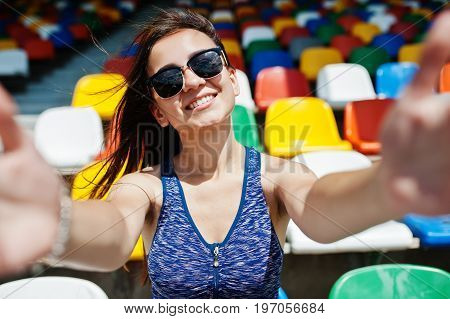 Close-up Portrait Of A Beautiful Fit Girl In Sunglasses Sitting In The Stadium.