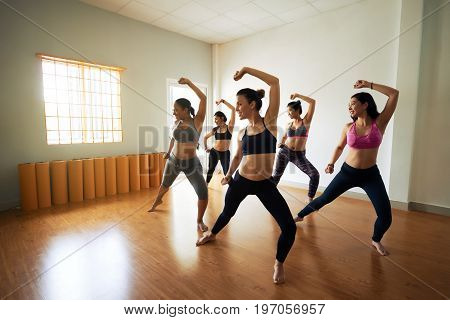 Group of joyful women wearing leggings and tops having fun while rehearsing dance in spacious studio