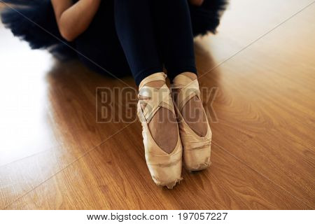Close-up of slim graceful legs of unrecognizable ballerina in worn-out pointe shoes