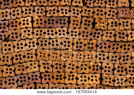 Abstract background of red clay block for wall construction. Texture of Clay brick wall design with holes.