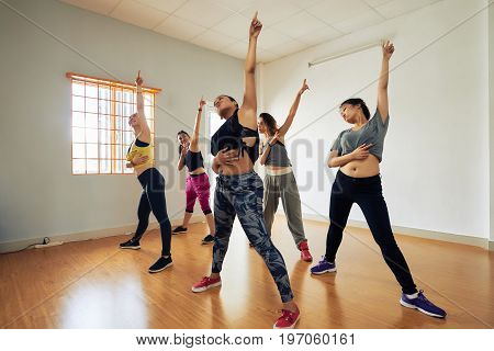 Attractive hip-hop dancers gathered together in modern dance hall in order to participate in final rehearsal