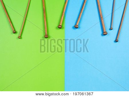 Wooden bamboo knitting needles arranged as frame border on colorful background. Top view.