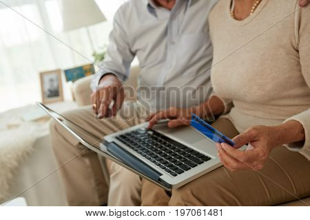 Cropped image of couple entering credit card information when shopping online