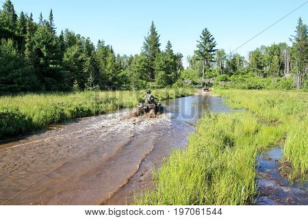 People driving ATV quad through dirty water in forest. Ontario, Canada.