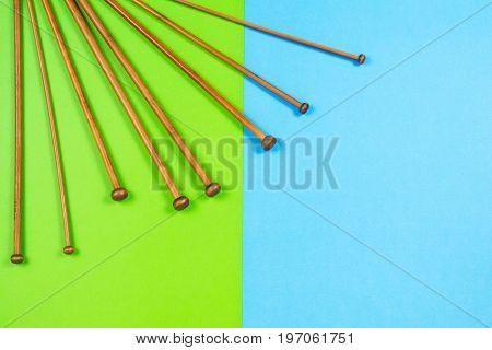 Variety of bamboo knitting needles in different sizes on colorful background. Top view