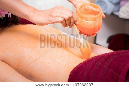 Spa Therapist putting orange Spa scrub on to women back