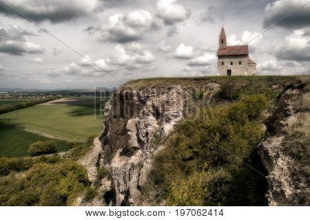 Romantic Drazovsky church on the hill Slovakia. Cloudscaoe over dark country