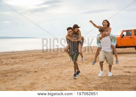 Two happy young couples having fun together at the beach