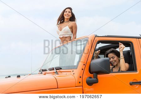 Two attractive young women laughing and having fun while driving a car at the beach