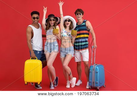 Picture of young cheerful group of friends standing isolated over red background. Looking at camera holding suitcases and cocktails.