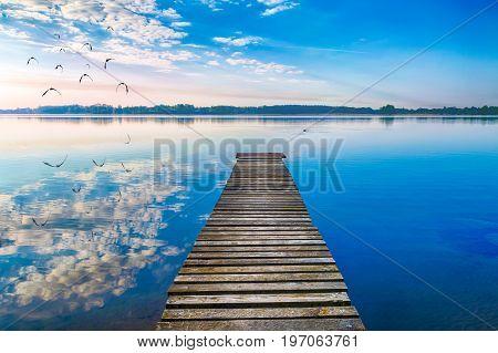 EBirds fly over empty footbridge. The lake Selment Wielki Masuria Poland.