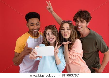 Image of young cheerful group of friends standing isolated over red background. Looking aside make selfie by phone.