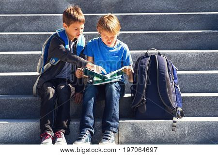 Schoolboys doing homework outdoors. Back to school concept.