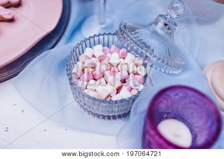 Colorful mini marshmallows in Glassware on a white table with blue lace. Different mini white and pink puffy marshmallows. Marshmallow concept. Selective focus