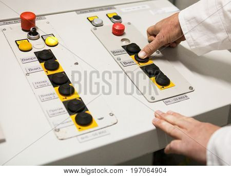 Male hand pushing the button on the control panel of the industrial plant. Close up.