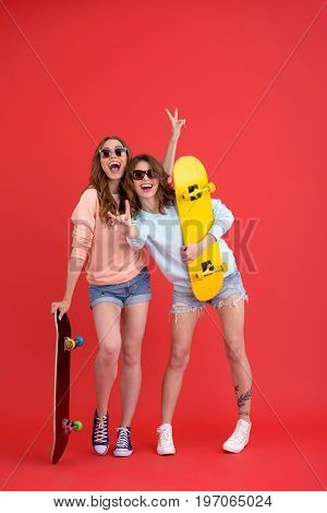 Image of young happy two ladies friends standing isolated over red background. Looking at camera holding skateboards.