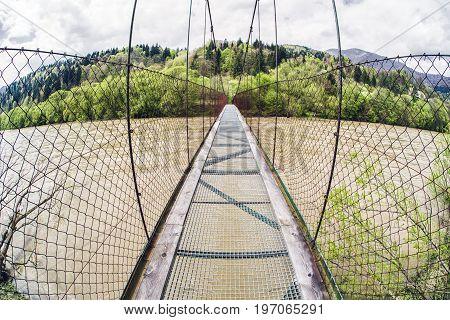 Long empty pedestrian bridge over river Orava at Slovakia