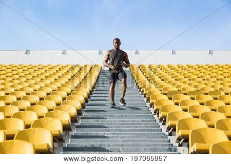 Concentrated young man running downstairs on stadium