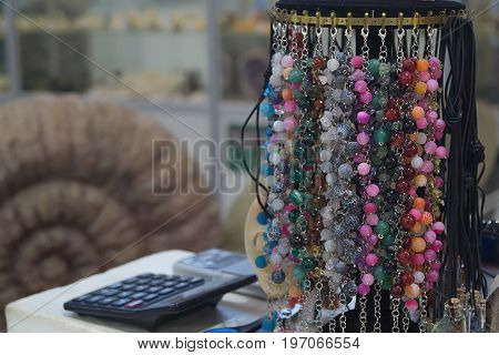 Bracelets of multi-colored stones on the counter of the store with calculator and ancient shell on the background