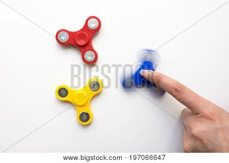 Hand Spiner. Stress relieving toy on white background. Close-up. Top view. Stock photo.