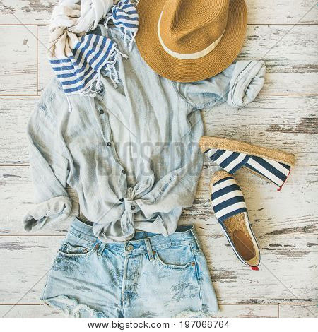 Summer outfit flatlay. Pastel coloured summer women's clothes, parquet background, top view, square crop. Blue shorts, linen shirt, straw hat, yellow bag, sunglasses, striped neckerchief, espadrillas