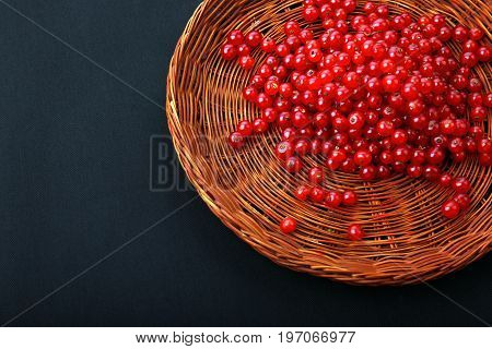 A view from above on a red currant in a wicker wooden basket on a black background. Juicy and bitter red currants in a brown crate. Appetizing ingredients for vegan cocktails.