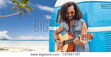 summer holidays, travel, music and people concept - young hippie man playing guitar at minivan car over tropical beach background