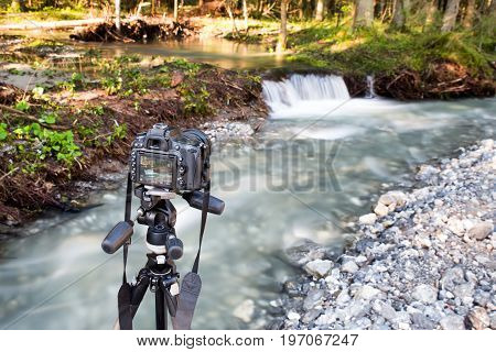 Outdoor photoshooting river with camera on tripod