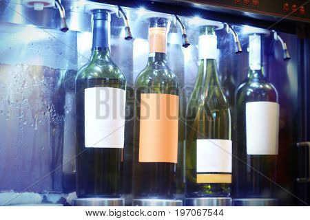 Dispenser with opened bottles of wine in cellar, closeup