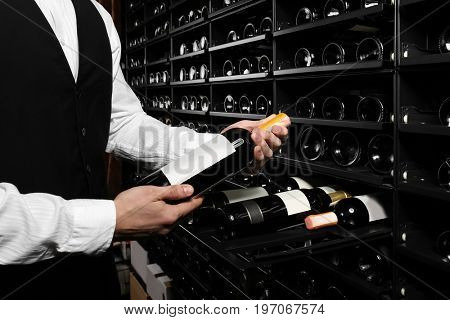 Sommelier with wine bottle near rack at store