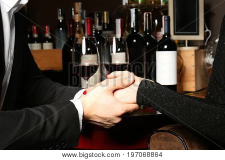 Couple holding hands together on date at wine degustation