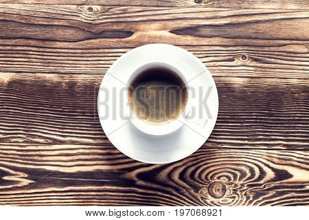 Coffee cup and cookie on wood