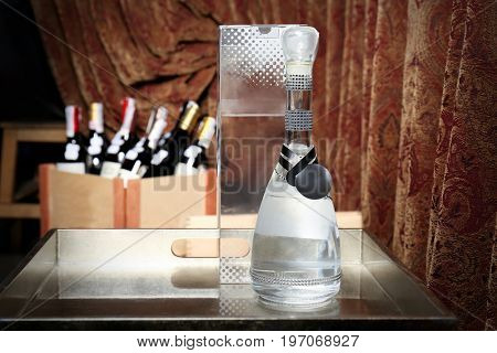 Bottle of grappa on tray in winery store