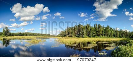 Reflections in blue water of beautiful lake. Mirrowed clouds and landscape. Ontario, Canada.
