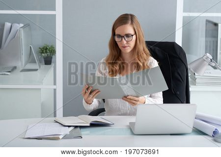 Serious business lady in glasses reading document in a folder