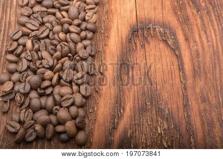 Coffee bean background on wooden texture. Coffee beans on wooden background. Brown coffee seeds. Old table with coffee grains. Imported coffee from India.